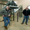 From the left: William Runkle, wastewater director and Josh Farley, wastewater superintendent stand near a centrifugr used to separate water from sludge on Tuesday at the Center Creek Wastewater Treatment facility.<br /> Globe | Laurie SIsk