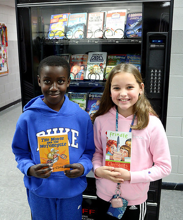 Kangwa Cloud and Allison Case, students at Grove Upper Elementary School, show off the books they picked out from the school's new book vending machine. <br /> Globe   Kaylea M. Hutson-Miller