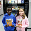Kangwa Cloud and Allison Case, students at Grove Upper Elementary School, show off the books they picked out from the school's new book vending machine. <br /> Globe | Kaylea M. Hutson-Miller