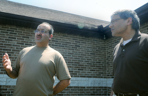 Globe/Roger Nomer<br /> Iftikhar Ali, president of the Islamic Center of Joplin, left, and Asadulah Ahmed, a member of the center, talk about a fire which damaged the roof of the center, which can be seen behind the two men on the corner, during an interview on Wednesday.