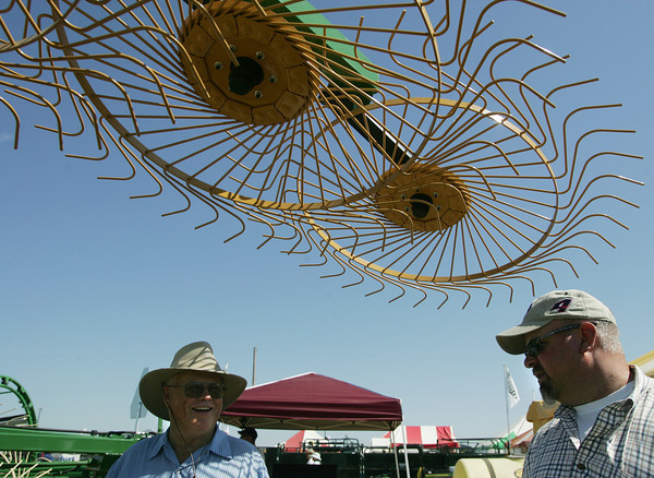 Globe/Roger Nomer<br /> Don Jones, Neodesha, Kan., left, talks with Brian Frick, with Price Brothers Equipment in Wichita, about a carted hay rake at the Four State Farm Show on Friday.