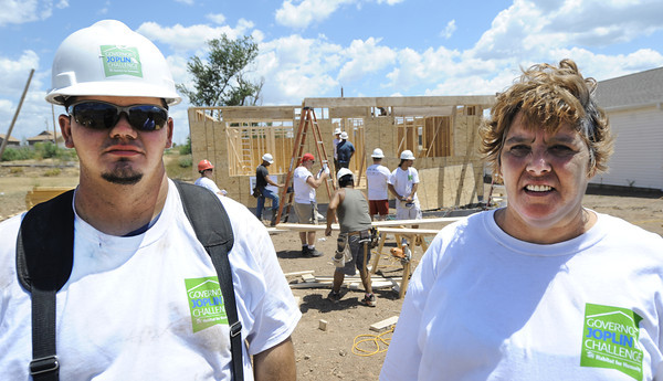 Globe/T. Rob Brown<br /> Michelle Wilson, right, and her son Dakota Wilson, stand in front of their future home while a group of volunteers from the St. Louis Blues help build the Habitat for Humanity home Wednesday afternoon, July 25, 2012, near the intersection of 25th Street and Picher Avenue.