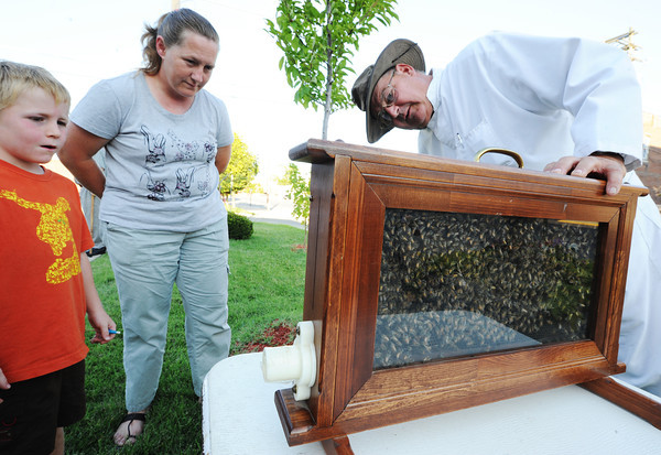 Globe/T. Rob Brown<br /> Webb City beekeeper Jann Amos, right, shows off part of his hive Saturday evening, July 21, 2012, during the dedication ceremony for the new downtown Webb City mural to Webb City residents including Laura Davis and her six-year-old son, Robert Davis.