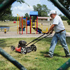 Globe/T. Rob Brown Steve Anthony, Joplin Parks & Recreation Department groundskeeper, mows the grass Tuesday afternoon, July 3, 2012, at Landreth Park in preparation for the Fourth of July activities.