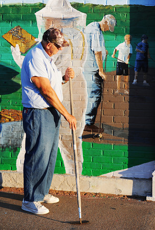 Globe/T. Rob Brown<br /> Dale Mermoud, of Carthage, stands with hoe-in-hand next to his likeness in the new downtown Webb City mural Saturday evening, July 21, 2012, during the mural's dedication ceremony.