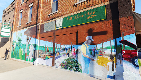 Globe/T. Rob Brown<br /> Eileen Nichols, director of the Webb City Farmers' Market, takes down an old notice and places a new one, bearing the identity of the donars for the new downtown Webb City mural Saturday evening, July 21, 2012, just before the mural's dedication ceremony.