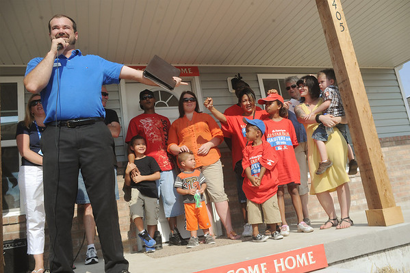 Globe/Roger Nomer<br /> Scott Clayton, executive director for Joplin Area Habitat for Humanity, introduces the three families receiving new homes on Connor Street on Friday afternoon.