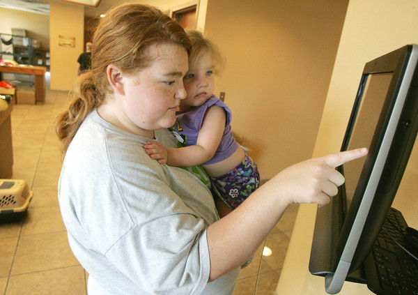 Globe/Roger Nomer<br /> Chelsea and Autumn, 2, Nuse, Carthage, check an interactive kiosk for a new pet at the Joplin Humane Society on Tuesday.