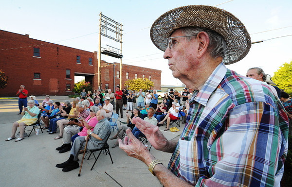 """Globe/T. Rob Brown<br /> Bob Nichols, right, of Webb City, who identifies himself as, """"the proud father of Eileen,"""" (Eileen Nichols, director of the Webb City Farmers' Market) claps during the dedication ceremony for the new downtown Webb City mural Saturday evening, July 21, 2012."""