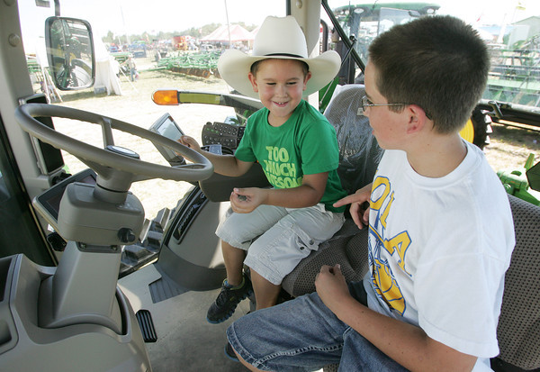 Globe/Roger Nomer<br /> Isaac, 5, and Elijah, 11, Hopkins, Iola, Kan., take in the view of the Four State Farm Show from the high cab of a combine on Friday.