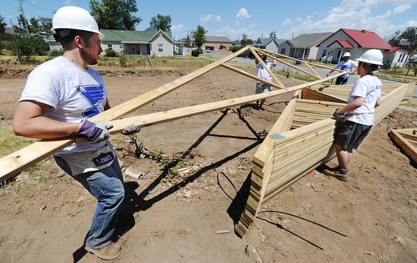 Globe/T. Rob Brown<br /> Andrew Horwat, left, St. Louis Blues mascot coordinator, works with other St. Louis Blues employees as they move trusses for a Joplin Area Habitat for Humanity home under construction Wednesday afternoon, July 25, 2012, near the intersection of 24th Street and Picher Avenue.