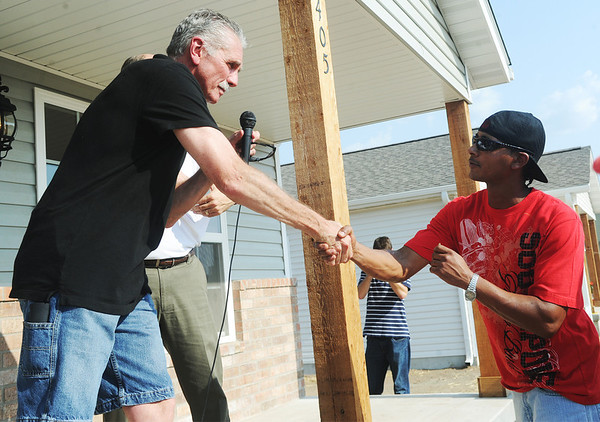 Globe/Roger Nomer<br /> Former Major League player Steve Rogers presents a key to Stephen Gutierrez for his new Habitat home on Friday.