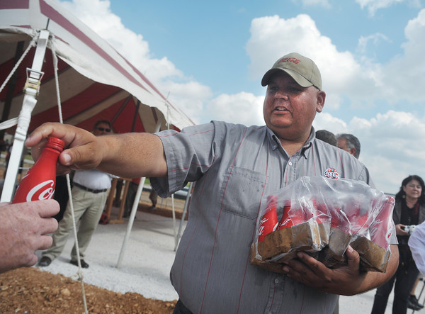 Globe/Roger Nomer<br /> Alie Watkins, who works in the service department at Coca Cola, passes out chilled bottles of Coke to the crowd at Monday's groundbreaking.