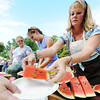 Globe/T. Rob Brown<br /> Patty Krueger, right, Newton County circuit clerk, hands out slices of juicy watermelon Tuesday evening, July 31, 2012, during the annual Republican Women of Newton County watermelon feed in Neosho's Big Spring Park. Charlotte Ward, Newton County auditor, is at center in background.