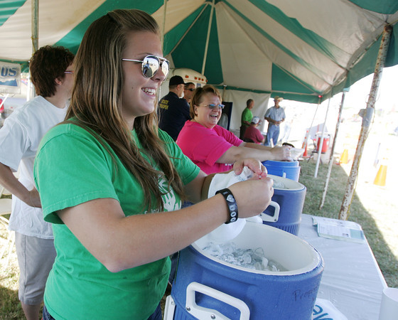 Globe/Roger Nomer<br /> Jennifer Dunlap, and her mother Jeanette Dunlap, a mobile mammography coordinator with Mercy, hand out cold, water-soaked towels at the Mercy Health booth at the Four State Farm Show on Friday.