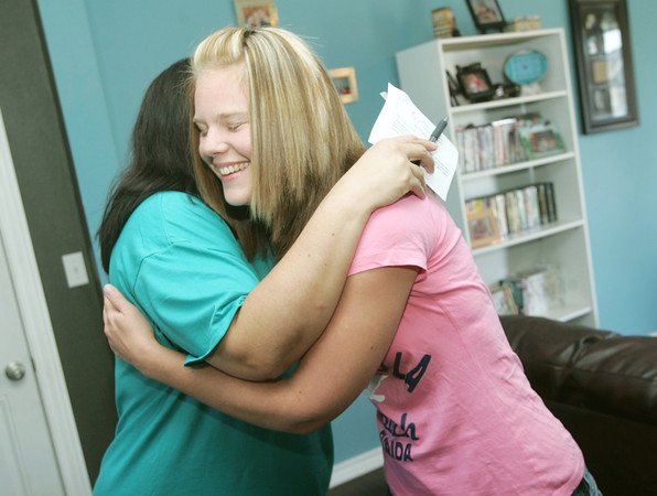 Globe/Roger Nomer<br /> Emily Russell gets a hug from Norma Hernandez, a case manager with Catholic Charities before receiving the keys to her house on Friday.