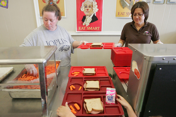 Globe/Roger Nomer<br /> Arlene Warren, left, and Linda Rivera serve lunch at Columbia Elementary for a YMCA camp on Thursday.
