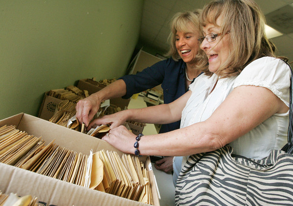 Globe/Roger Nomer<br /> Marcia Long, left, and Kathi Cassady, Joplin, react to finding Cassady's wedding photos in the Mosler archive at the Joplin Museum Complex on Tuesday.  Long is Murwin Mosler's daughter on hand to help with the archival distribution.