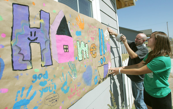 Globe/Roger Nomer<br /> Larry Jump helps Abbie Demmitt, Troy, Ohio, hang a welcome home sign on the Jump's new home on Friday.  Demmitt is part of the Experience Mission group which help with the rebuild of Jump's house.