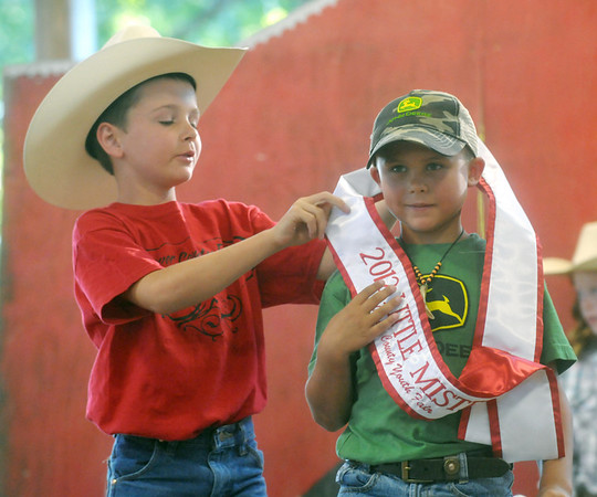 Globe/Roger Nomer<br /> Country Little Mister 2011 Cody Peters secures the sash for this year's Country Little Mister Shaun Hunt at the Jasper Country Fair on Tuesday.
