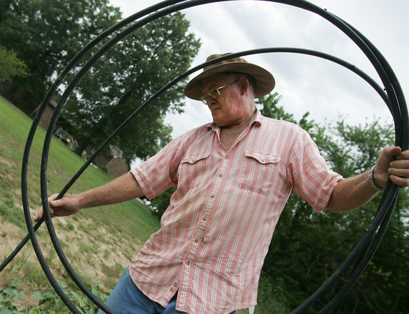 Globe/Roger Nomer<br /> Ed Cook lays down a drip hose on his garden near Liberal on Thursday morning.