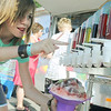 Globe/Roger Nomer<br /> Lauren Gower, 14, Joplin, finds it hard to choose just one flavor for her shaved ice during Joplin's Fourth of July celebration at Landreth Park on Wednesday.