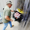 Globe/T. Rob Brown<br /> Crosslines Pantry Manager Konrad Fehrenbach, of Joplin, brings in a load of donated apples Friday afternoon, July 13, 2012.