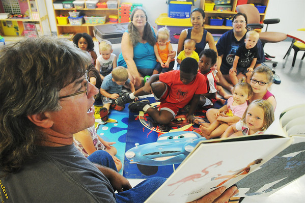 Globe/Roger Nomer<br /> Ray Malcom reads to a group of children at the Kids Korner Daycare on Thursday morning.