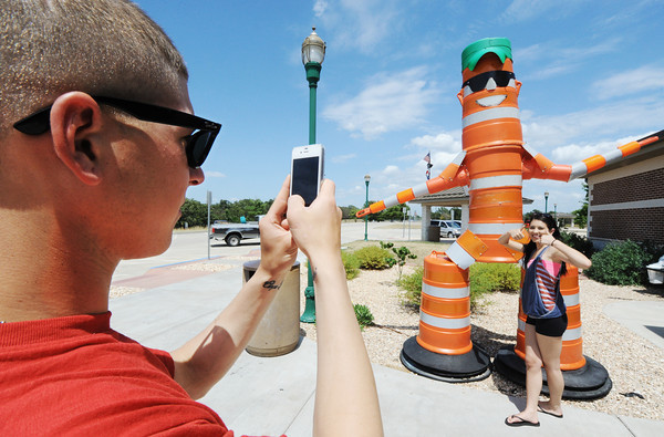 Globe/T. Rob Brown Codey Garaux, left, takes a phone photo of his wife, Amanda Garaux, at the Missouri Welcome Center on I-44 in Joplin, as she gives a thumbs-up for the camera next to the center's icon Barrel Bob Monday afternoon, July 2, 2012. The couple said they were traveling home from El Paso, Texas, to Canton, Ohio. Codey Garaux is on leave from the U.S. Army.