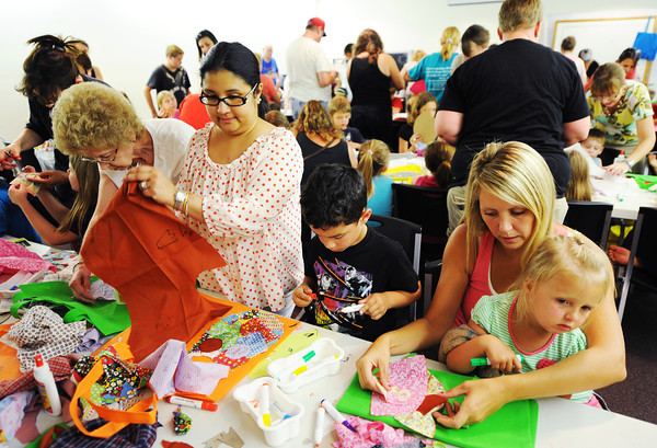 """Globe/T. Rob Brown<br /> Kasey Overman, right, of Quapaw, Okla., and daughter Madison Overman, 3, work on a book tote bag alongside Pam Bhend, of Joplin, and son David Bhend, 4, Thursday afternoon, July 12, 2012, in a crowded meeting room at the Joplin Public Library during an arts and crafts session. """"We come to all of these craft events at the library,"""" Overman said. """"They're all packed."""" Cherokee Vinson, children's assistant at the library, said they had to turn away 23 children from the event due to space constraints."""