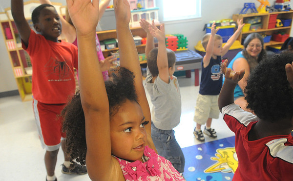 Globe/Roger Nomer<br /> Alexis Conner, 7, stretches for the sky during morning exercises at Kids Korner Daycare on Thursday morning.