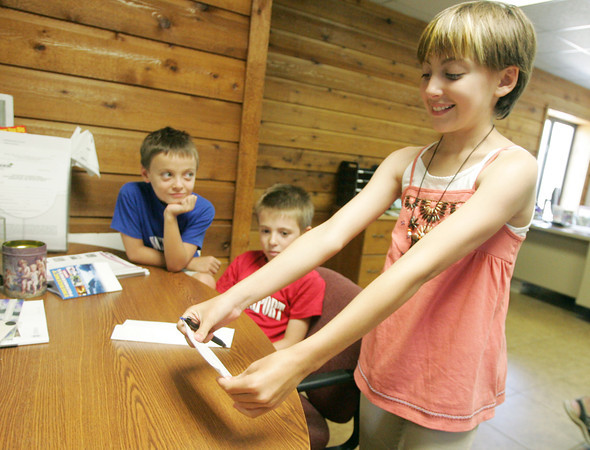Globe/Roger Nomer<br /> After signing her check for $800, Sarah Conner proudly admires her contribution to Joplin as brothers William, left, and James, 9, look on.