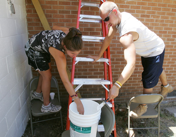Globe/Roger Nomer<br /> Katie Rohrscheiv, 18, Clinton, Ill., and Michael Jahns, Ripon, Wis., paint trim at Journey Church in Joplin as part of a service project with Next Step Ministries on Wednesday afternoon.