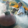 Globe/Roger Nomer<br /> Smoke pours from a Kamado Joe grill as Richard Hulsey, from Sutherlands in Joplin, right, shows demonstrates it for Mike Fast, Pittsburg, at the Four State Farm Show on Friday.