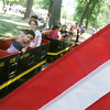 Globe/Roger Nomer<br /> An American flag waves in the breeze as the kiddie train at Lincoln Park rolls past during Pittsburg's Fourth of July celebration on Wednesday.