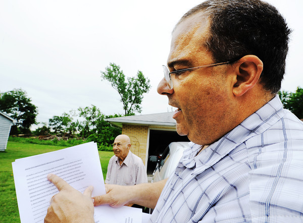 Globe/T. Rob Brown Richard Martinous, of Joplin, son of Mose and Kathy Martinous, who both live on the property, reads legal papers regarding what he believes is an illegal dumping operation at Bullfrog Mine.