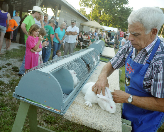 Globe/Roger Nomer<br /> Tex Thomas judges a rabbit entry at the Jasper County Youth Fair on Tuesday.