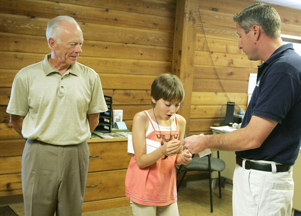 Globe/Roger Nomer<br /> Charles Keeter, vice chairman of the Joplin Tree Board, and Chris Cotten present Sarah Connor with some pins in recognition of her contribution to Joplin on Wednesday.