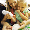 "Globe/T. Rob Brown<br /> Kasey Overman, of Quapaw, Okla., holds her 3-year-old daughter Madison Overman as they glue decorative fabric on a book tote bag Thursday afternoon, July 12, 2012, in a crowded meeting room at the Joplin Public Library during an arts and crafts session. ""We come to all of these craft events at the library,"" Overman said. ""They're all packed."" Cherokee Vinson, children's assistant at the library, said they had to turn away 23 children from the event due to space constraints."