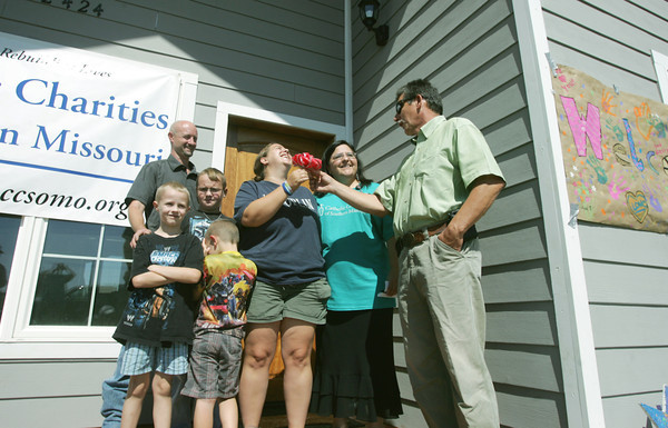 Globe/Roger Nomer<br /> Gabe Tischler, diaster coordinator with Catholic Charities, and Norma Hernandez, a case manager with Catholic Charities, hand over keys to the Jump family, including (from left) Caden, 7, Larry, Conner, 8, Lucas, 4, and Amy on Friday.