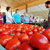 Globe/T. Rob Brown Hector Troyer (right), owner of Troyer's Vegetables of Stark City, speaks with a group of ladies as they wait in line to purchase from his large quantity of tomatoes Friday morning, June 29, 2012, at the Webb City Farmers' Market.