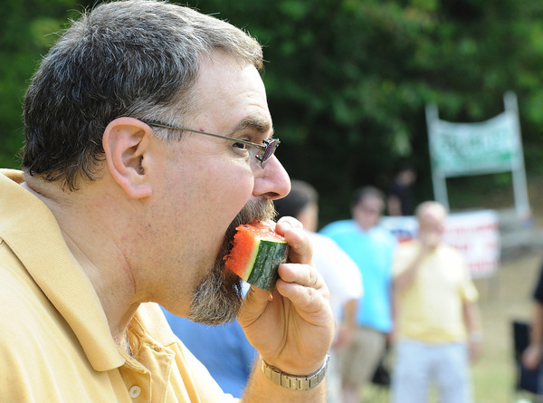 Globe/T. Rob Brown<br /> Russ Hively, of Neosho, bites into a piece of juicy watermelon Tuesday evening, July 31, 2012, during the annual Republican Women of Newton County watermelon feed in Neosho's Big Spring Park.