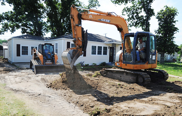 Globe/T. Rob Brown<br /> Shyann Wilson (left), bobcat operator with Camcor Environmental of Stella, and coworker Travis Oxendine remove dirt during lead remediation Tuesday afternoon, July 9, 2013, in the 2800 block of Virginia Avenue.