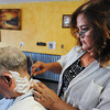 Globe/T. Rob Brown<br /> Deanna Thompson, owner and barber at Thompson's Barber Shop in the 900 block of South Main Street, shaves the neck of customer Jim Muskrat of Joplin Tuesday morning, July 30, 2013. Business is starting to trickle back after losing business during the demolition of the collapsed building on her block.