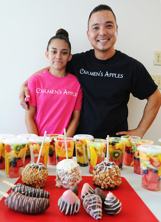 Globe/T. Rob Brown<br /> Eric Stuhlman and his 14-year-old daughter Ana Stuhlman, both with Carmen's Apples, stand behind a variety of fruit-related products Thursday morning, July 18, 2013, in their home kitchen.