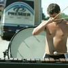 Globe/Roger Nomer<br /> Eric Jones, with the Music City Drum Corp. based out of Nashville, Tenn., wipes away sweat as he practices the marimba outside of North Middle School on Tuesday.  The drum corp was on their way to a performance in Bentonville, Ark., and stopped in Joplin for a midday practice.