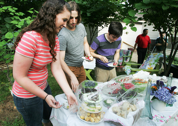 Globe/Roger Nomer<br /> (from left) Missouri Southern students Lindsey Sjurlund, Webb City senior, Brad Fordham, Clever senior, and Luke Barr, Joplin senior, select snacks during an English Tea Party for returning students who visited Europe this summer.