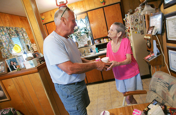 Globe/Roger Nomer<br /> Jim Wilkinson gives a meal to Norma Naylor during a visit on Tuesday morning.