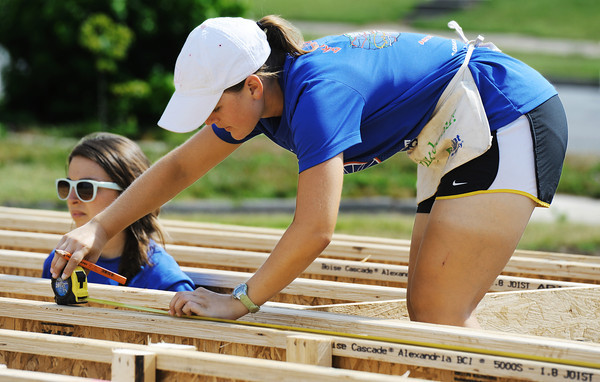 Globe/T. Rob  Brown<br /> Emily Baker (right) of Staunton, Va., takes a measurement as Tessa Mandra of Nashua, N.H., looks around, both with Bike & Build, while working on a Habitat for Humanity home in the 2300 block of Joplin Street Tuesday morning, July 23, 2013.