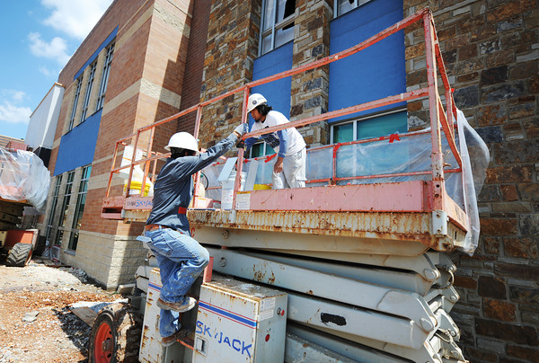 Globe/T. Rob Brown<br /> Angel Gutierrez (left) and Pedro Urbano, both with Midwest Drywall, work from a Skyjack to add the blue material to the sides of the building Tuesday, July 16, 2013, at the new Irving Elementary School.